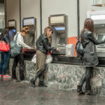Four girl friends withdrawing money from credit card at ATM. Business woman